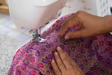 Woman sews strips of fabrics with sewing machine