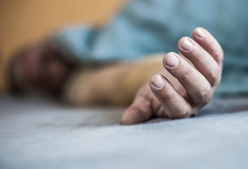 the outstretched arm of a man lying in a bed