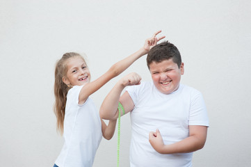 funny thin small girl measuring smiling fat boy muscle by tape fooling around