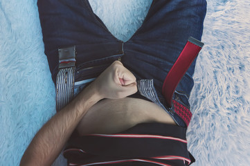 man masturbate, guy lies on the couch and holds his hand near the fly open on his jeans. Playful male hand touching his panties