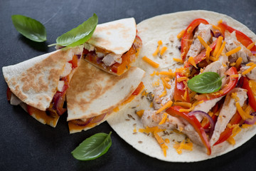 Closeup of quesadilla stuffed with grilled chicken meat, vegetables and cheddar, selective focus