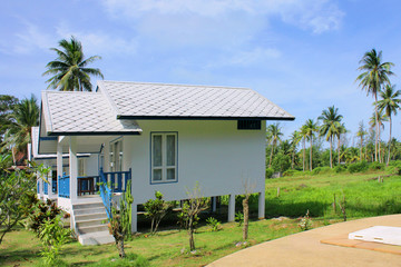 Beautiful small white house and tropical resort with blue sky on the beach and sea in Thailand