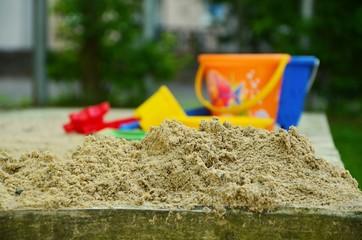 playground sand pit bucket plastic toys orange yellow blue water rain kids children outdoor park childcare kindergarden