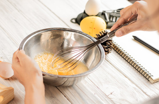 Female chef whisking eggs in  bowl on white table