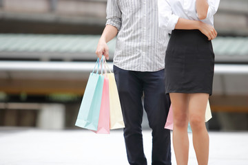 Cropped image of young couple carrying colorful shopping bags outdoors.