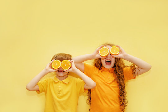 Laughing kids with orange eyes shows white healthy teeth