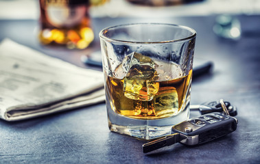 Car keys and glass of alcohol on table in pub or restaurant