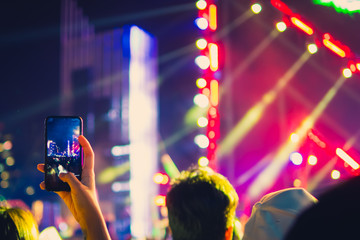 People who hold a smartphone and take a photo of the concert.Music Festival Party New Year Party.