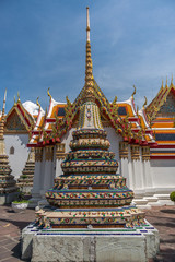 A colorful chedi in the Wat Pho temple in Bangkok. Beautifully decorated temple roofs in the background.