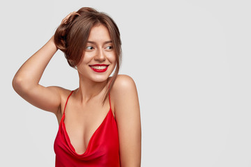 Sideways shot of cheerful fashion model collects luxurious hair, wears red lipstick, looks positively aside, shows bare shoulders, likes to pose at camera, stands against white background, blank space