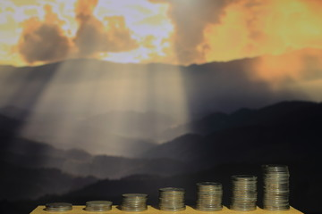 funding for environmental conservation.  pile of coins in increasing chart shape in front of dramatic god light beam from bursting cloud over mountain in the background.