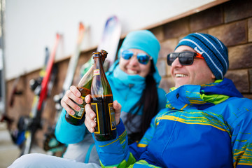 Photo of cheerful man and woman in sunglasses with beer on winter day