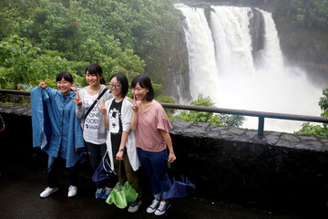 Tourists pose for a picture in front of a waterfall swollen by rain from Hurricane Lane in Hilo