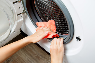 Photo of woman hands wiping cloth washing machine