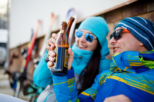 Photo of cheerful tourists with beer on winter day