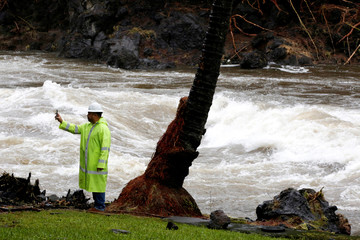 A Hawaii County employee photographs a river swollen by Hurricane Lane in Hilo