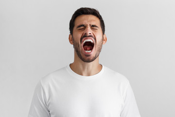 Screaming with closed eyes crazy young man in blank white t-shirt isolated on gray background