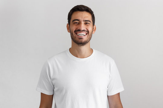 Horizontal shot of young positive european man isolated on gray background standing in blank white casual t-shirt looking straight at camera with happy smile, laughing