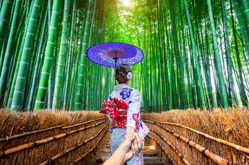 Fototapete - woman wearing japanese traditional kimono holding man's hand and leading him to Bamboo Forest in Kyoto, Japan.