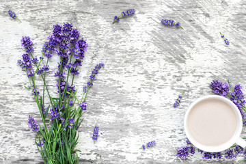 Lavender flowers bouquet with cup of cappuccino and frame made of flowers on rustic wooden...