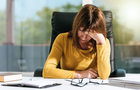 Desperate businesswoman with hand on forehead