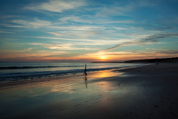 Sunset overlooking a beach in Normandy, France, with a girl doing a handstand.