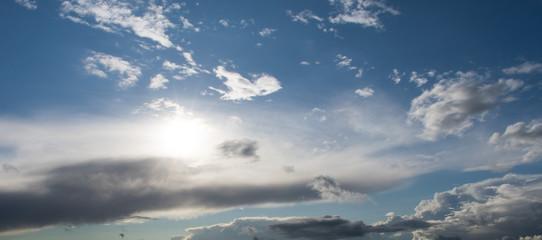 Wolkengebilde am frühen Abend mit Sonne