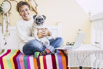 total happiness for beautiful cheerful caucasian young woman hugged with her best friends fat dog pug smiling too. friendship at home and enjoy lifestyle. bright and coloured image for love animals.