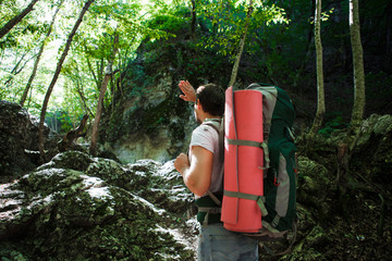 A man with a backpack and a karemate goes on a trek through the rocky gorge. Space for text.