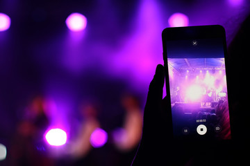 Shooting festival concert on smartphone with place for text. Blurred music stage bokeh background for design. Fans takes picture of scene on phone