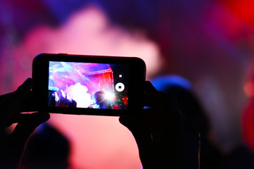 Shooting on smartphone festival concert. Blurred music stage bokeh background for design. Fans takes picture of scene on phone