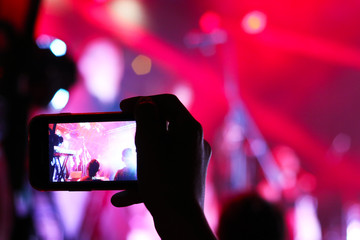 Smartphone shooting festival concert. Blurred music stage bokeh background for design. Fans takes picture of scene on phone