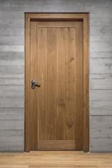 Modern quality wooden door in contemporary interior, Solid oak door with stainless steel handle set in concrete wall