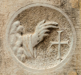 Blessing hand with cross, an ancient religious relief on a Venice wall