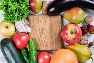 Empty wooden board with place for recipe. Healthy food fruits and vegetables on a white table. Top view. Flat lay.
