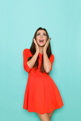 Excited Woman Is Mini Dress Is Holding Head In Hands, Looking Up And Shouting