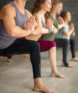 Group of male and female yoga beginners exercising against grey wall, doing yoga or pilates posture. Standing in Warrior pose, Virabhadrasana. Full length