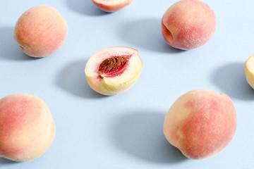 Whole ripe beautiful peaches and one split in half with putamen