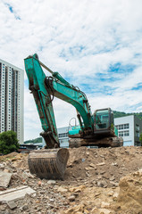 A large excavator transports building ruins at the construction site