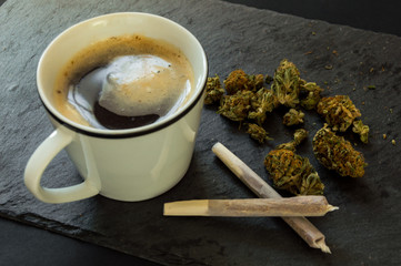 Delicious cup of coffee, a pile of high quality marijuana buds with two cigars of weed ready to smoke. Top view with background of black stone.