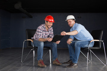 cheerful constructors are resting on the office chairs and holding the documents. full length photo. happiness concept. good mood at work