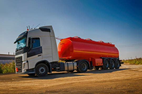 A truck with an orange tank goes on a knurled unpaved road