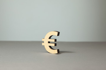 Euro symbol from wood on a gray background