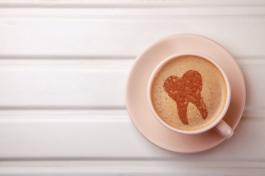 Cup of coffee with tooth on foam. Coffee spoils teeth and makes them yellow. Morning coffee