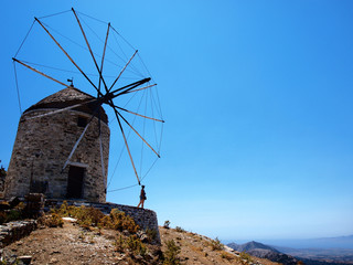 Girl watching the scenery in front of a classic old wind mill on a hill on Naxos island in Greece