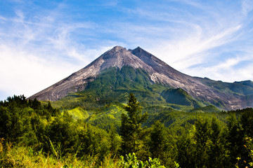 Scenic cone volcano with azure blue sky and clouds and green rainforest on Java island, Indonesia