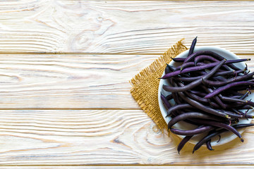 purple string beans on a wooden plate on a wooden background