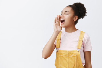 Girl shouting out loud to call friend come downstairs help her. Portrait of charming carefree urban female in yellow trendy overalls, turning left and holding palm near opened mouth, yelling