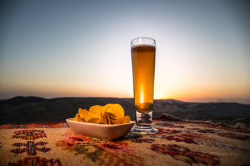 Close Up of A Glass of Beer with the snacks on Sunlight Background, beer on grass