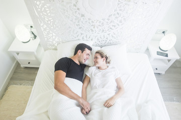 aerial view of beautiful caucasian young beautiful couple wake up at home in a white bed in the bedroom. stylish home and pretty people resting together with love and protection. moning lifestyle